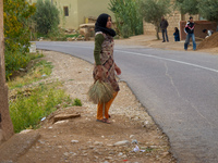 girls cleaning street Ait Arbi, Dades Valley, Morocco, Africa
