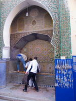 teenager muslims drinking from fountain Fez, Imperial City, Morocco, Africa